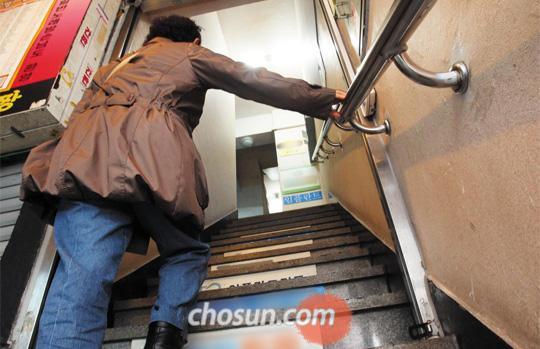 """지난 4일 아침 한 60대 할머니가 서울 종로구의 한 건물 3층에 있는 직업소개소로 가기 위해 힘겹게 계단을 오르고 있다. 이 할머니는 """"20년째 이곳에서 식당 청소나 설거지 등 허드렛일을 소개받아 생계를 잇고 있다고 했다. 이 할머니도 수천만원의 빚을 지고 있다고 했다. /이준헌 기자"""
