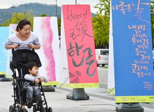 한글날을 앞두고 7일 오후 서울 세종로 광화문광장에서 열린'한글 멋글씨전'에서 한 여성이 유모차에 아이를 태우고 다양한 글씨체로 쓰인 한글 전시물을 구경하고 있다.