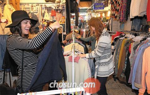 23일 서울 광장시장 수입 구제상가를 찾은 고객이 옷을 고르고 있다. 최근 가격이 저렴하고 멋스러운 구제 의류를 찾는 젊은 소비자가 많아졌다