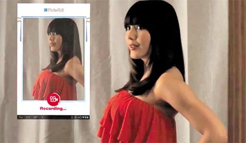 미국 여배우 셀레스티 도슨이 의류 매장의 디지털 미러 앞에서 옷을 입자 SNS를 통해 보낼 이미지가 거울 위에 만들어지고 있다.