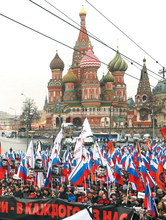 """1일 플래카드와 깃발을 든 시민들이 모스크바의 대표 관광 명소 바실리크 대성당 주변을 행진하고 있다. 플래카드엔 """"이 총탄은 우리 모두를 향한 것이다"""" """"영웅은 결코 죽지 않는다""""고 적혀 있다. 이들은 지난 27일 모스크바 도심에서 살해된 야당 지도자 보리스 넴초프 전 러시아 부총리를 추모하기 위해 모였다. '푸틴 최대의 정적(政敵)'이라 불리던 넴초프가 바실리크 대성당에서 멀지 않은 크렘린궁 부근에서 괴한 총에 맞고 살해된 이후, 러시아에선 추도 집회가 잇따라 열리고 반(反)푸틴 시위가 확산될 조짐을 보이고 있다"""