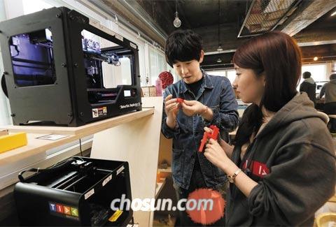 지난 16일 서울 종로구 세운전자상가에 있는 시제품 제작 공간 '팹랩서울'에서 스타트업(창업 초기 기업) '닷'의 디자이너 주재성(왼쪽)씨와 타이드인스티튜트 최아름 연구원이 3D프린터로 만든 스마트시계 부품을 살펴보고 있다.