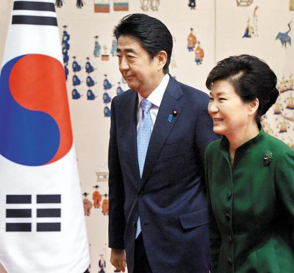 """박근혜 대통령이 2일 청와대에서 아베 신조(왼쪽) 일본 총리와의 정상회담에 앞서 기념 촬영을 한 뒤 회담장으로 걸어가고 있다. 두 정상은 이날 """"가능한 한 조기에 위안부 피해자 문제를 타결하기 위한 협의를 가속화하자""""고 합의했다."""