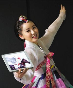 조각보로 만든 한복을 입은 김현정 작가. 태블릿PC 안 그림은 한복 차림으로 승마하는 여인을 그린 작품이다.