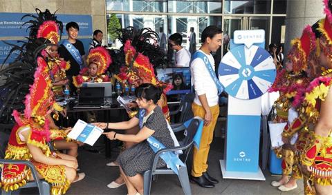 22일 인천 중구 축구전용경기장에서 열린 '필리핀의 날' 축제에 참가한 센트비 직원들이 퍼레이드를 위해 화려하게 차려입은 필리핀 사람들에게 온라인 송금 서비스를 알리고 있다.