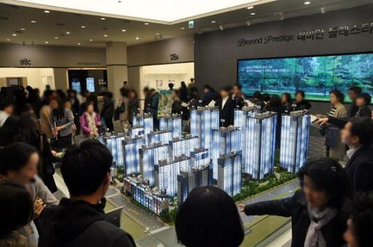 개포 주공 2단지를 재건축한 개포 래미안 블레스티지 견본주택(모델하우스)에서 관람객들이 단지 모형도를 살펴보고 있다. /조선일보DB