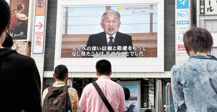 8일 일본 도쿄 시민들이 대형 스크린 앞에서 발길을 멈추고 아키히토(明仁) 일왕이 생전 퇴위 의향을 밝히는 영상을 바라보고 있다. 아키히토 일왕은 건강상 이유를 들어 더 이상 일왕으로서 임무를 수행하기 어렵다는 대국민 메시지를 발표했다.