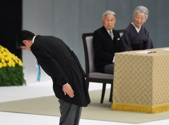 15일 일본 도쿄에서 열린 전국 전몰자 추도식에서 아베 신조총리가 제단을 향해 고개를 숙이고 있는 것을 아키히토(明仁) 일왕 부부가 지켜보고 있다./AFP=연합뉴스