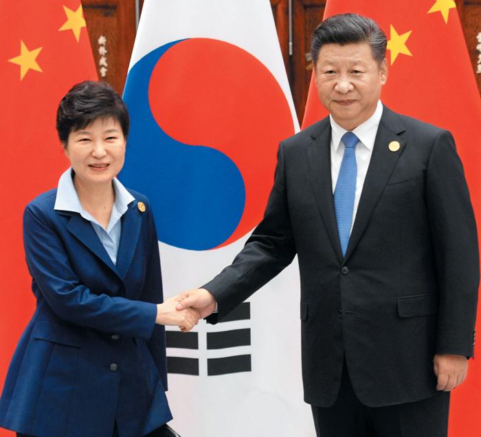"""사드 배치 결정 후 첫 회담 - 박근혜 대통령과 중국 시진핑 국가주석이 5일 중국 항저우에서 열린 한·중 정상회담에서 만나 악수하고 있다. 시 주석은 이날 비공개 회담 시간에 """"미국이 한국에 배치하는 사드(고고도 미사일 방어체계) 시스템에 반대한다""""는 입장을 밝혔고, 이에 대해 박 대통령은 """"북핵 및 미사일 문제가 해결되면 (사드는) 더 이상 필요가 없을 것""""이라고 말했다."""