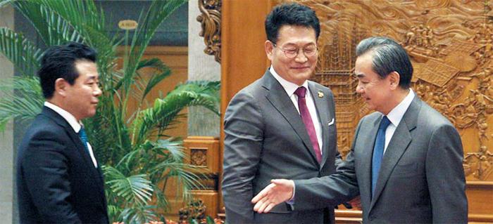 왕이 외교부장의 환대 - 왕이(오른쪽) 중국 외교부장이 4일 중국 베이징 외교부 감람청에서 송영길(가운데) 더불어민주당 의원, 박정 의원을 만나 인사를 하고 있다. 중국은 사드(고고도 미사일 방어 체계) 문제를 논의하겠다며 방중한 민주당 의원 7명에게 고위급 면담과 만찬을 베푸는 등 환대했다.