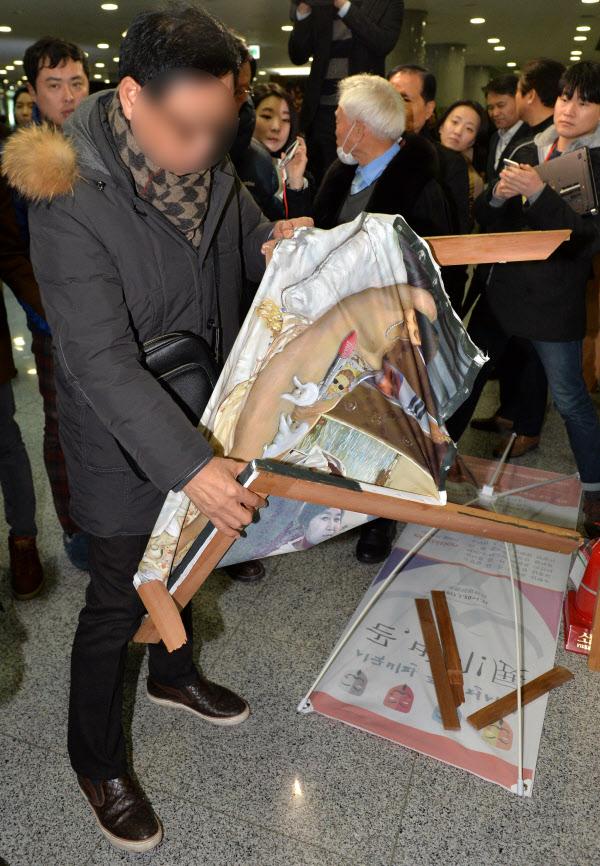 뉴시스  24일 오후 서울 여의도 국회 의원회관 1층 로비에서 한 박근혜 대통령 지지자가 훼손된 이구영 작가의 '더러운 잠'을 들어보고 있다.
