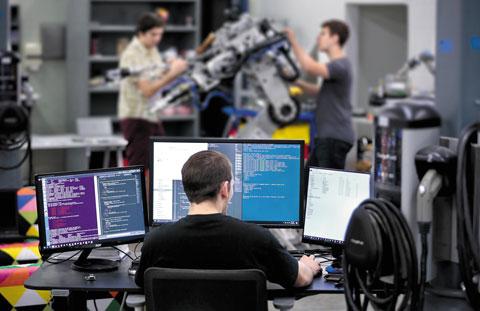 캐나다 인공지능(AI) 로봇업체'킨드레드'소속 연구진들이 지난해 7월 미국 샌프란시스코에 있는 연구실에서 AI 장착 로봇을 점검하는 모습.