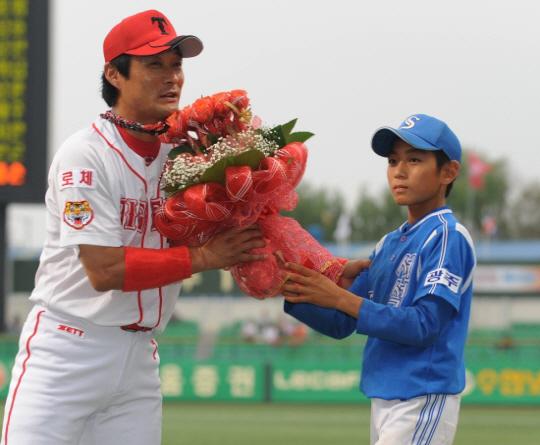 현역 시절 이종범(왼쪽)과 아버지에게 꽃다발을 건네고 있는 서석초 시절 이정후. 스포츠조선DB