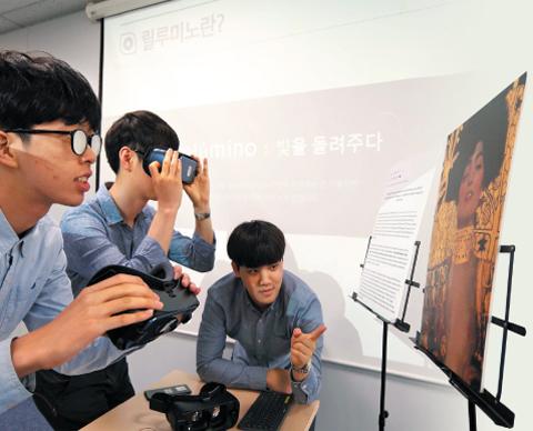 18일 서울 중구 삼성전자 브리핑룸에서 삼성전자 사내 벤처팀 관계자들이 시각 장애인의 시력을 재현하는 특수 안경을 쓴 채로(왼쪽 2명) 시각 장애인용 앱 '릴루미노'를 시연하고 있다. 이들이 손에 들고 있는 가상현실 기기 '기어VR'을 쓰고 그림을 바라보면 릴루미노가 기어VR 전면의 스마트폰 카메라를 통해 들어온 영상을 시각 장애인들이 볼 수 있는 형태로 바꿔준다.