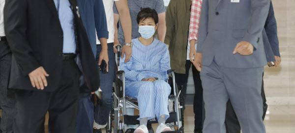 환자복을 입은 박근혜 전 대통령이 30일 서울 서초동 서울성모병원에서 허리 통증으로 진료를 받은 뒤 휠체어를 타고 병원을 나서고 있다. /연합뉴스