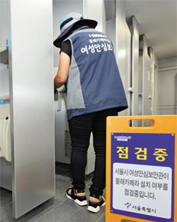 서울시 여성 안심 보안관이 여자 화장실 앞에 '점검중' 푯말을 세우고 몰카가 있는지 탐지하고 있다. 이들은 전자파·적외선 탐지기로 화장실 곳곳을 점검한다.