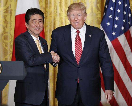 지난 2월 미국 백악관에서 도널드 트럼프 미국 대통령과 아베 신조 일본 총리가 기자회견장에서 만나 악수하고 있다./연합뉴스