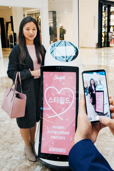 7일 복합 쇼핑몰 스타필드 하남에서 한 고객이 LG전자가 개발한 안내 로봇과 함께 기념사진을 찍고 있다.