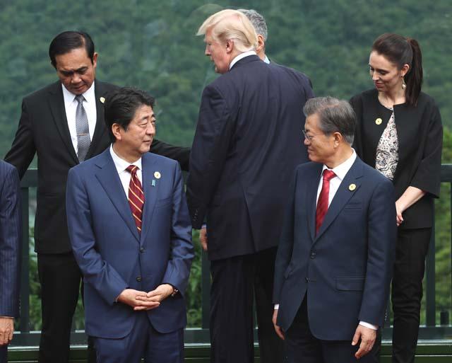 11일 오후(현지시각) 베트남 다낭 인터컨티넨탈 호텔에서 열린 아시아태평양경제협력체(APEC) 정상회의에서 아베 신조 일본 총리와 문재인 대통령이 촬영장으로 이동하는 도널드 트럼프 대통령을 보고 있다. /뉴시스