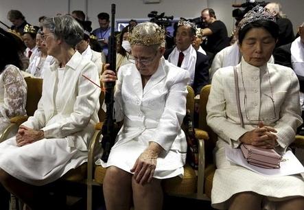 하얀 원피스에 왕관을 쓴 여성이 한 손에 AR-15 소총을 든 채로 합동결혼식에서 예배를 하고 있다. /AP 연합뉴스