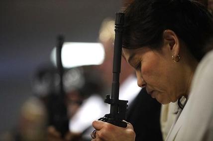 2018년 2월 28일(현지 시각) 합동결혼식에 참석한 신도들이 한 손에 AR-15 소총을 들고 있다. /AFP 연합뉴스