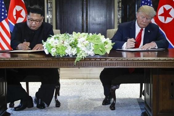 12일(현지시각) 싱가포르 센토사섬 카펠라호텔에서 도널드 트럼프 미국 대통령(오른쪽)과 김정은 북한 국무위원장이 합의문에 서명하고 있다. /AP·연합뉴스