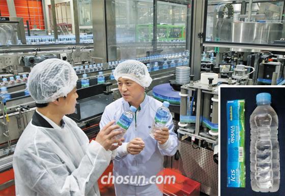 물에 담그면 분리되는 라벨  - 경기도 연천 백학음료 공장에서 임일환(오른쪽) 공장장이 물에 잘 분리되는 라벨을 부착하는 공정을 설명하고 있다. 작은 사진은 라벨이 분리된 롯데칠성음료 생수병.