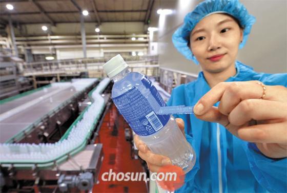 '드드드득' 손으로 뜯어지는 라벨 - 동아오츠카 청주 공장 직원이 절취선을 적용해 재활용하기 쉽게 만든 '블루 라벨' 페트병을 들고 라벨을 떼어내는 과정을 보여주고 있다.