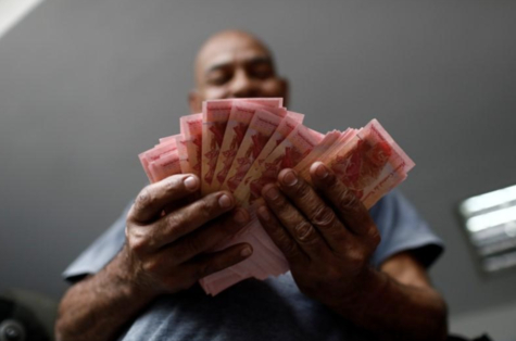 볼리바르 화폐를 세고 있는 근로자의 모습. /로이터