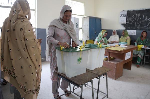 25일(현지 시각) 파키스탄 이슬라마바드의 한 투표소에서 한 여성이 투표함에 투표용지를 넣고 있다. /연합뉴스