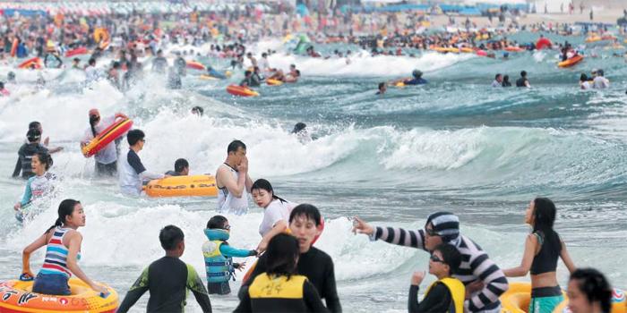 휴가 절정… 어제 50만명이 해운대로 - 29일 오후 부산 해운대구 해운대해수욕장에서 피서객들이 물놀이를 즐기고 있다. 부산시에 따르면 이날 50만명이 해운대해수욕장을 찾았다. 이 외에도 광안리, 송정 등 부산 해수욕장 7곳을 찾은 피서객은 이날 하루 총 214만3000명으로 올해 최대 인파를 기록했다.