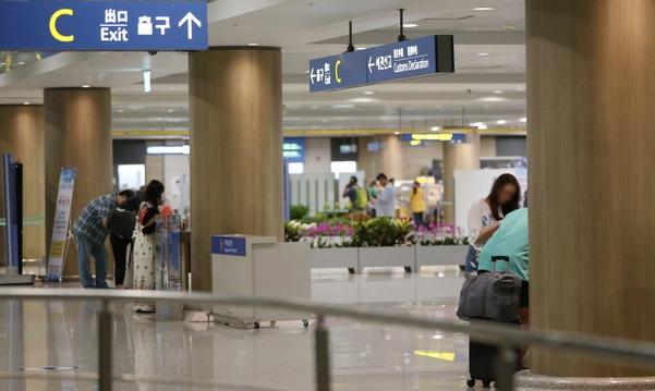 입국장 내 마련된 테이블에서 세관신고서를 작성하는 여행객들. /남강호 기자