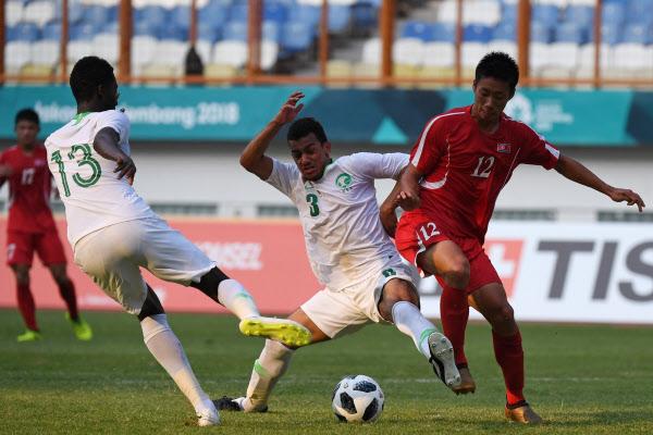 /AFP 연합뉴스 20일 열린 자카르타-팔렘방 아시안게임 남자 축구 F조 예선에서 북한과 사우디아라비아 선수가 공을 다투는 모습