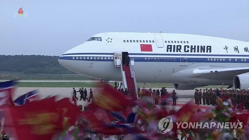 북한 조선중앙TV가 14일 방영한 북미정상회담 기록영화에서 김정은 북한 국무위원장이 중국 고위급 전용기를 이용해 싱가포르를 오간 사실을 소개했다. 사진은 기록영화 중 김 위원장이 평양국제비행장에 착륙한 전용기에서 내리는 모습. 항공기 몸체에 중국의 오성홍기와 '에어차이나'(중국 국제항공) 로고가 선명한 점이 눈길을 끈다. /연합뉴스