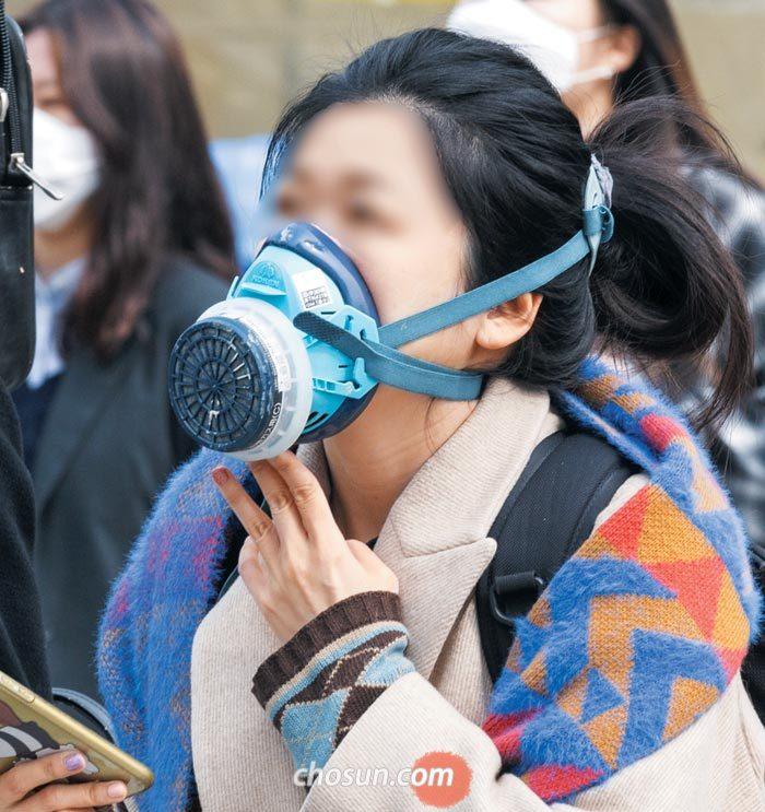 5일 서울 광화문에서 방독면을 방불케하는 대형 마스크를 쓴 여성이 길을 걷고 있다.