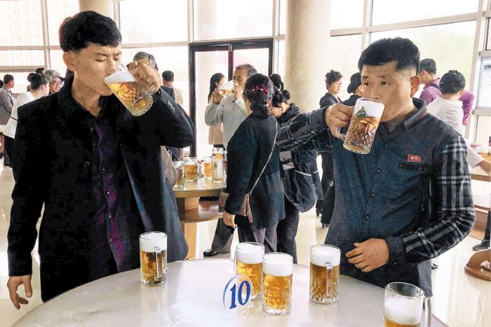 선 채로 생맥주 마시는 평양 주민들 - 북한 주민들이 지난 23일 평양 보통강변에 있는 '만수교 청량음료점'에서 선 채로 생맥주를 마시고 있다. 테이블 위에 맥주잔들이 가득하다. 최근 북한은 김정은 국무위원장의 지시로 유엔 등 국제사회에 식량난을 호소하고 있다.