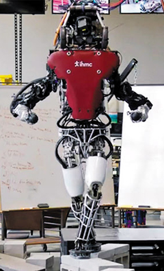 인간형 로봇 아틀라스가 자율차 기술과 인공지능을 이용해 좁은 블록 위를 걸어가고 있다.