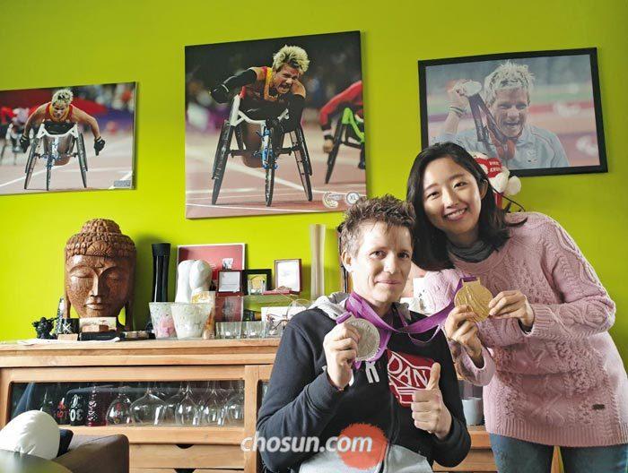 휠체어 육상 선수 마리케 베르보트(왼쪽)가 지난달 벨기에 디에스트에 있는 자신의 집에서 탐험대원 남혜윤씨를 만나 패럴림픽 메달을 들어 보이고 있다.