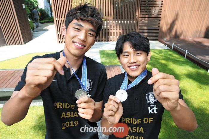 """오세훈(왼쪽)은 자신보다 한 달 늦게 태어난 조영욱(오른쪽)을 '영욱이 형'이라고 부른다. 조영욱이 학교를 일찍 들어가 1998년생들과 함께 졸업한 탓이다. 오세훈은 """"진짜 나이를 처음 알았을 땐 어색했지만, 리더십 있는 모습에 지금은 내가 먼저 '형'이라고 하게 된다""""고 했다. 17일 서울 중구에서 두 선수가 한 손에 은메달을 쥐고 다른 한 손으로는 팬을 향해 수줍게 '손가락 하트'를 만들어 보인 모습."""