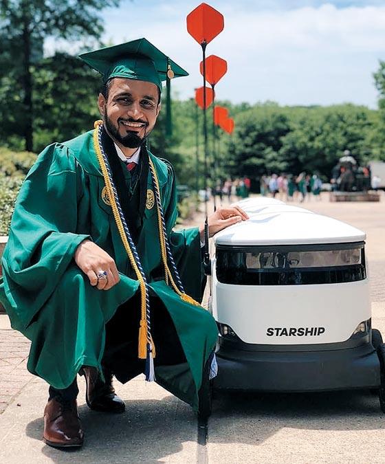 미국 조지 메이슨대학 졸업생이 아침 식사를 배달하는 로봇 곁에서 포즈를 취한 모습.