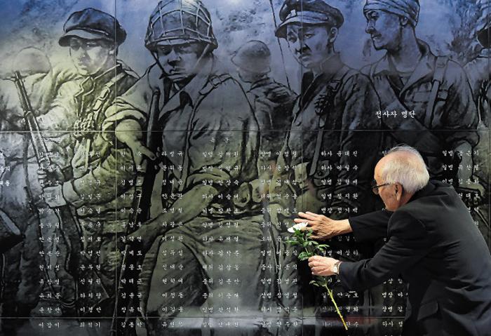 """오늘 6·25전쟁 69주년… """"전우여, 우리 싸움은 헛되지 않았다"""" - 6·25전쟁 발발 69주년을 하루 앞둔 24일 경기도 수원시 현충탑을 찾은 6·25 참전 용사가 전사자 명단 앞에 헌화하고 있다. 이날 해외 참전 용사들도 국립 서울현충원을 참배했다. 이들은 """"발전한 오늘의 한국을 보니 우리의 싸움이 헛되지 않았다""""고 말했다."""