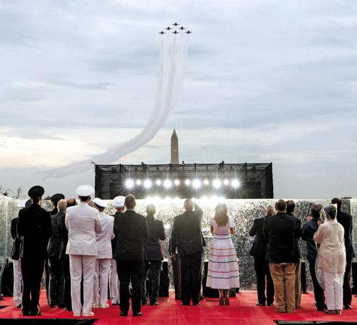 4일(현지 시각) 미국 워싱턴DC에서 열린 독립기념일 행사에서 도널드 트럼프 미 대통령 부부(가운데) 등 참석자들이 무대에 서서 곡예비행단 블루에인절스 F-18 전투기의 공중분열을 바라보고 있다. 이날 행사에는 에이브럼스 탱크와 브래들리 장갑차, B-2 전략폭격기와 F-35 전투기 등 각 군을 대표하는 무기들이 선을 보였다.