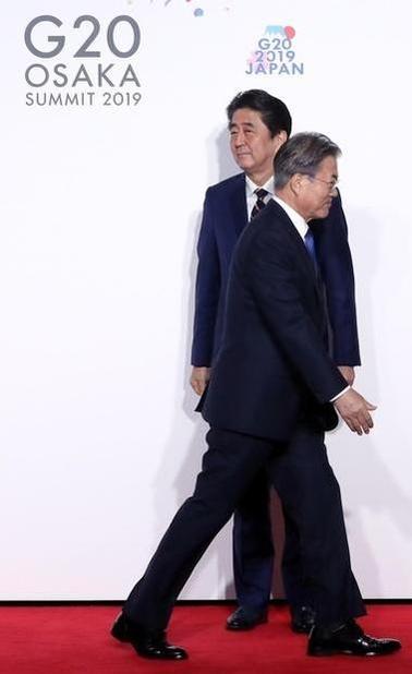 문재인 대통령이 2019년 6월 28일 오전 인텍스 오사카에서 열린 G20 정상회의 공식환영식에서 의장국인 일본 아베 신조 총리와 악수한 뒤 이동하고 있다. /연합뉴스