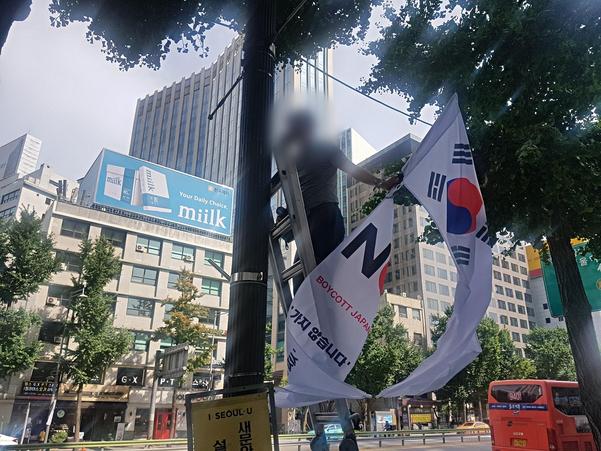 6일 오후 3시 30분쯤 서울 중구 대한문 인근 도로에 내걸었던 '노 재팬(No Japan)' 깃발이 철거되는 모습. /류인선 인턴기자