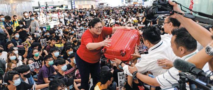시위대에 둘러싸인 출국자 - 반중(反中) 시위대가 13일(현지 시각) 홍콩 국제공항 출국장을 점거하고 연좌 농성을 벌이는 가운데 탑승 수속을 밟으려는 한 여성이 자신의 여행용 가방을 공항 보안 직원에게 건네고 있다. 경찰의 강경 시위 진압에 항의하는 수천명의 시위대가 이날 오전부터 공항에 몰려 오후 4시 30분부터 탑승 수속이 전면 중단됐고 모든 출발편 운항이 취소됐다.