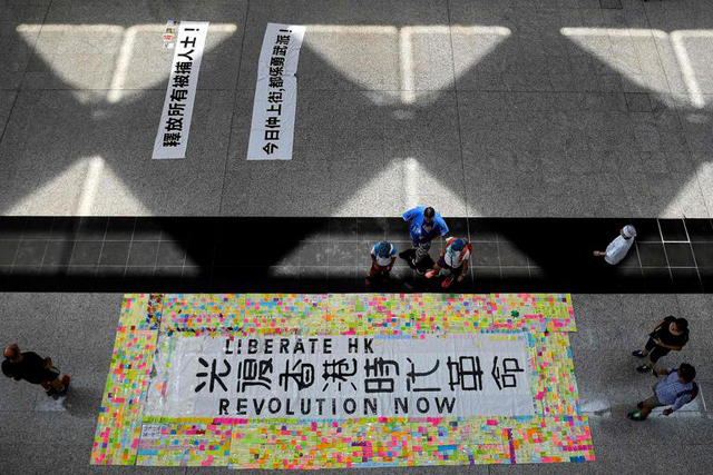 11일 범죄인 인도법(일명 송환법) 반대 연좌 농성이 벌어진 홍콩 국제공항 로비 바닥에 '홍콩의 해방'을 뜻하는 '광복홍콩(光復香港)'의 문구를 오가는 사람들이 일고 있다/ 홍콩 AFP=연합뉴스