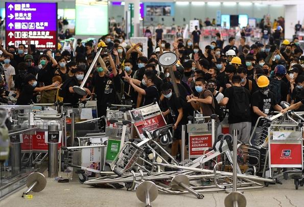 지난 13일 홍콩국제공항에 모인 시위대가 공항 기물을 이용해 공항 터미널 입구를 막고 있다./연합뉴스