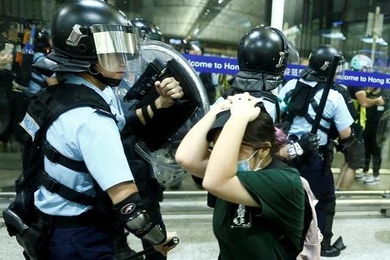 13일 홍콩 국제공항에서 홍콩 경찰이 시위대를 진압하고 있다. /로이터 연합뉴스
