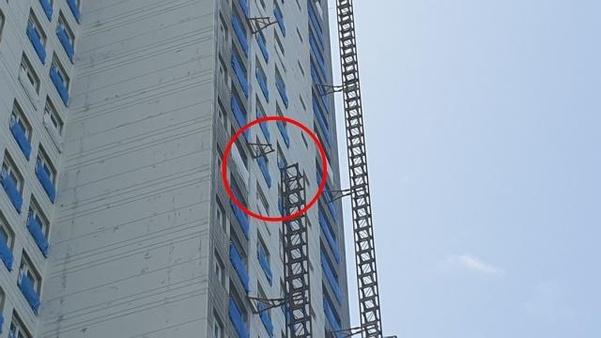 14일 강원 속초시의 한 아파트 공사 현장에서 건설용 리프트 추락 사고가 나 6명의 사상자가 발생했다. 리프트가 떨어진 15층 지점의 모습. 외벽에 붙어 지지대 역할을 하는 월타이가 끊겨 있고, 해체되다 만 마스트(빨간 원) 잔해가 보인다. /속초=배미래 인턴기자