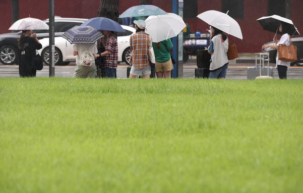 12일 오전 서울 중구 프레스센터 앞에서 우산을 쓴 시민과 관광객들이 버스를 기다리고 있다. /연합뉴스